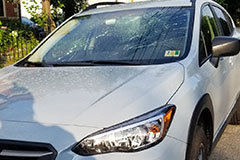 white subaru SUV front windshield smashed in broken vandalis