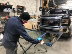 GMC truck front windshield replace at Wizard Auto Glass with technician working and wearing protective facemask and gloves for safety during coronavirus COVID 19