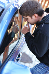 auto glass fixer repairing the side window of the blue sedan by Wizard Auto Glass