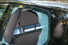 back window glass of black sedan is broken from thief smashed it in